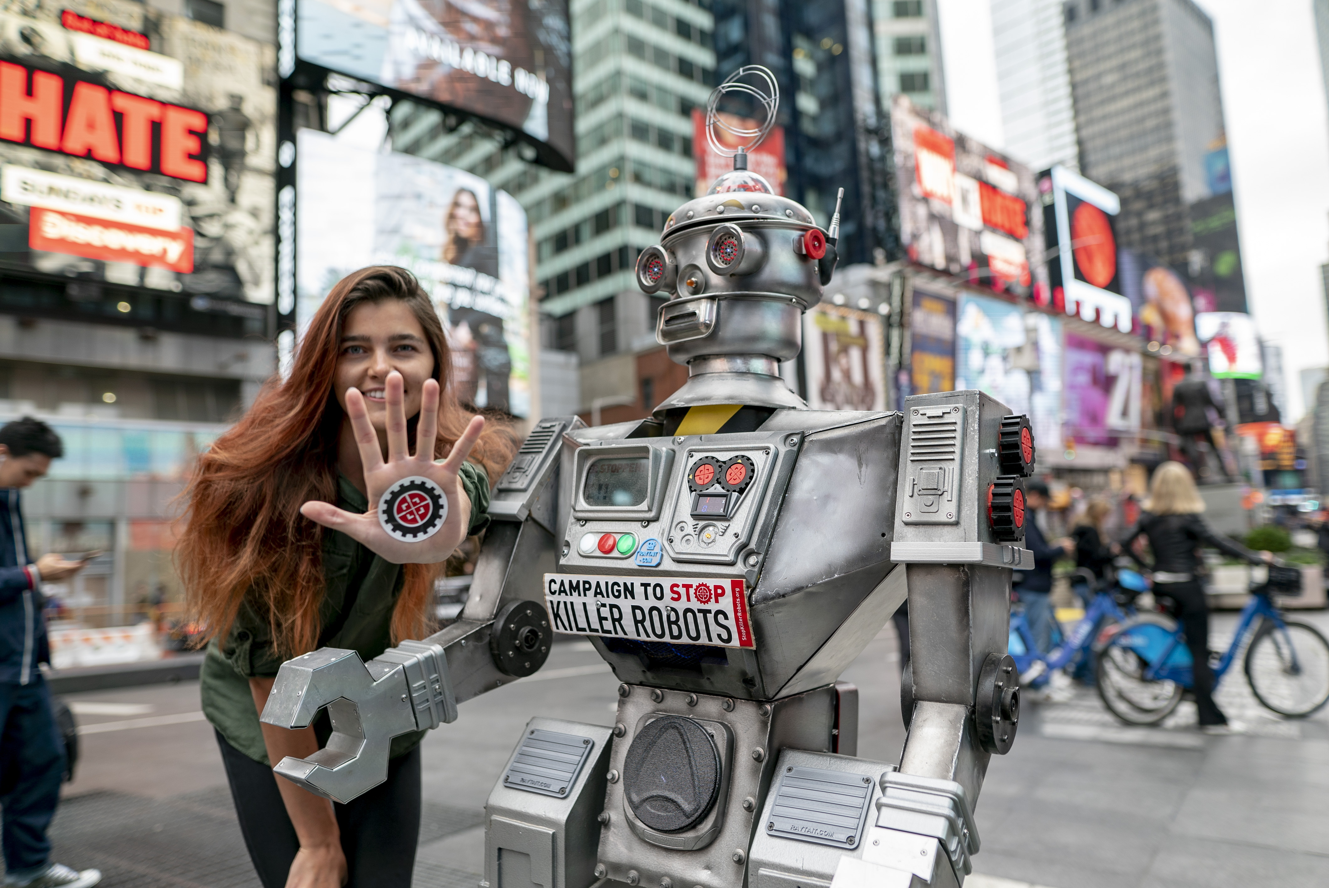 A campaigner poses with a robot in Times Square.